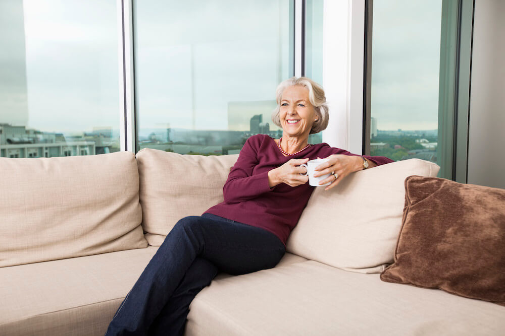 Smiling senior woman with coffee mug relaxing on sofa at home
